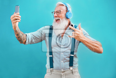 Bild Senior hipster man using smartphone app for creating playlist with rock music - Trendy tattoo guy having fun with mobile phone technology - Tech and joyful elderly lifestyle concept - Focus on face