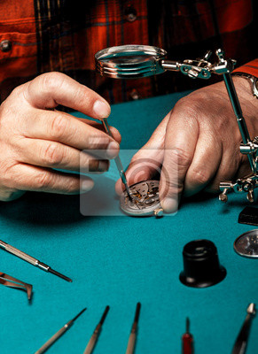 Bild Senior watchmaker repairing an old pocket watch