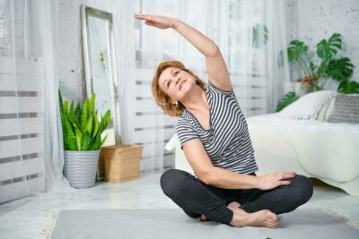 Bild Senior woman exercising while sitting in lotus position. Active mature woman doing stretching exercise in living room at home.