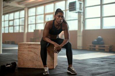 Bild Serious ethnic female athlete resting near dumbbells