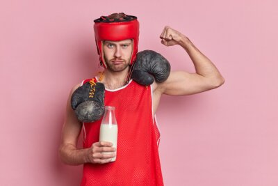 Bild Serious male boxer raises arm shows biceps drinks fresh milk to be strong wears protective hat red t shirt boxing gloves around neck demonstrates power isolated over pink background. Be healthy