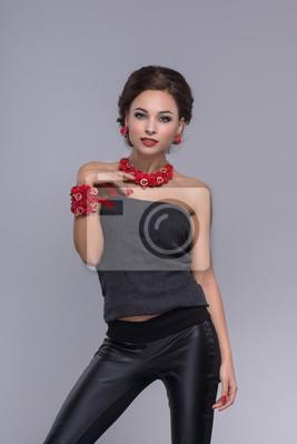 Sexy Brünette posiert in engen schwarzen Hosen und T-Shirt auf einem grauen Hintergrund. Suchen Sie nach einer Kamera
