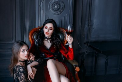 Bild Sexy gothic woman vampire evil sitting on armchair holding glass of wine blood. bloody makeup sharp teeth fangs red lips. vintage medieval dress. frightened scared girl victim obeys at feet mistress