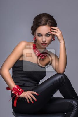 Sexy Mädchen posiert im Studio in schwarzem T-Shirt und einem stilvollen Zubehör.
