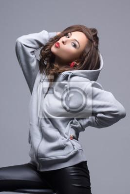 Sexy Mädchen posiert und lächelnd im Studio im Sport-Sweatshirt. Sieht zur Kamera