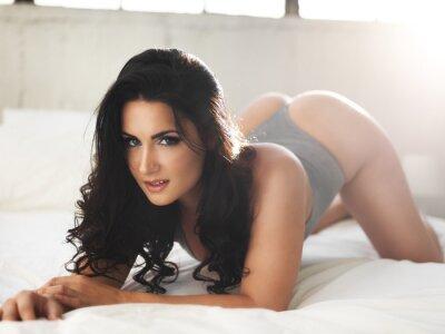 Bild Sexy Modell auf hell beleuchteten Bett in erotischen Pose