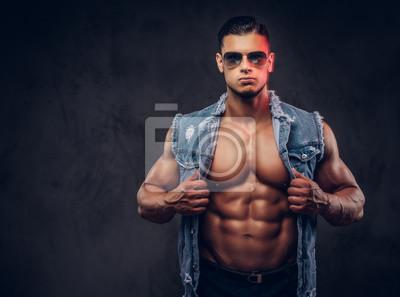 Bild Sexy nackter moderner athletischer Mann in einer Denimweste und -sonnenbrille wirft in einem Studio auf.