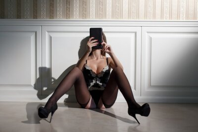 Bild Sexy woman reading messages on tablet at vintage wall