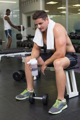Shirtless bodybuilder holding protein drink sitting on bench