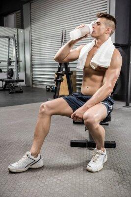 Shirtless Mann auf der Bank trinken Protein-Shake