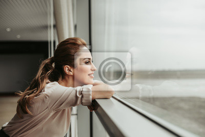 Bild Side view happy woman dreaming while looking at window indoor. She having rest during labor