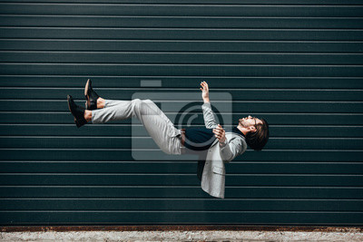 Bild side view of handsome young businessman with briefcase falling in front of roller gate