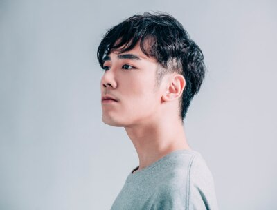 Bild side view of young  asian handsome man isolated on gray background