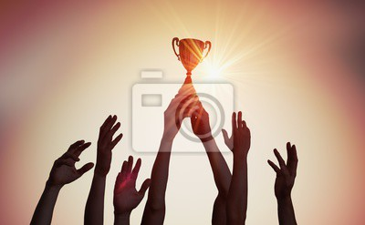 Bild Siegermannschaft hält Trophäe in den Händen. Schattenbilder vieler Hände im Sonnenuntergang.