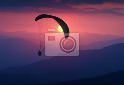 Silhouette der fliegenden Gleitschirm im Licht des Sonnenaufgangs