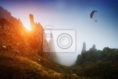 Silhouette des Gleitschirm über das neblige Bergtal
