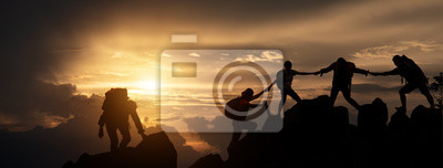 Bild Silhouette of Hikers climbing up mountain cliff. Climbing group helping each other while climbing up in sunset. Concept of help and teamwork, Limits of life and Hiking success full.