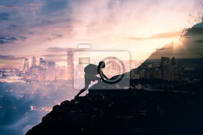 Bild silhouette of man climbing up mountain overlooking city