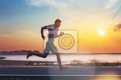 Bild Silhouette of man running sprinting on road. Fit male fitness runner during outdoor workout with sunset background