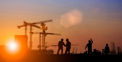 Bild Silhouette of Survey Engineer and construction team working at site over blurred  industry background with Light fair Film Grain effect.Create from multiple reference images together