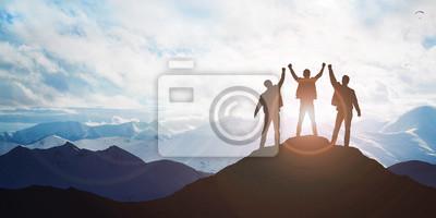 Bild Silhouette of the team on the peak of mountain