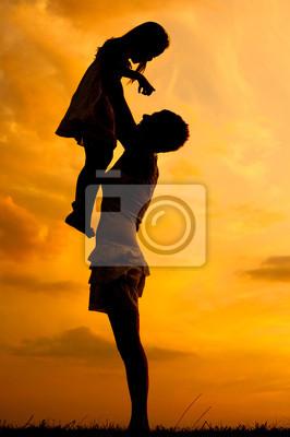 Silhouetten der glücklichen Mutter und Tochter bei Sonnenuntergang