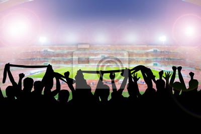 Silhouetten von Fußball-Fans im Stadion während des Spiels