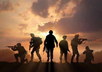 Bild Six military silhouettes on sunset sky background