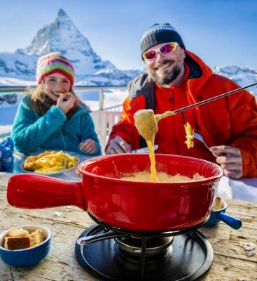 Bild Skifahrer in einem Restaurant, Fondue, traditionelle Schweizer Küche - Matterhorn in den Schweizer Alpen im Hintergrund