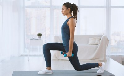 Bild Slim Hispanic girl doing lunges with dumbbells at home, empty space