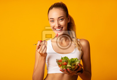 Bild Slim Young Woman Eating Salad From Bowl On Yellow Background