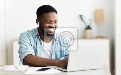 Bild Smiling african-american guy in earphones studying foreign language online