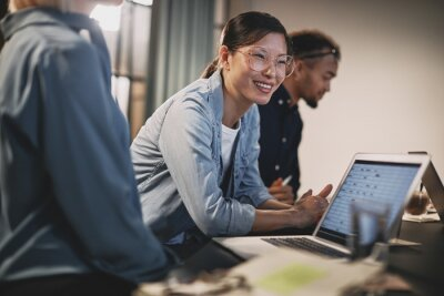 Bild Smiling Asian businesswoman meeting with coworkers in an office