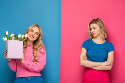 Bild Smiling girl holding bouquet near envy blonde sister on blue and pink background