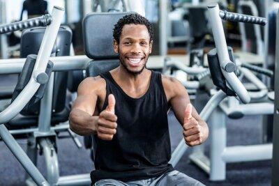 Smiling Mann mit Daumen nach oben mit Übungsgerät