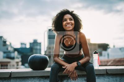 Bild Smiling woman athlete taking a break during workout