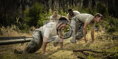 Soldaten, die unter dem Netz während des Hindernislaufs kriechen
