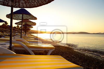 Sonnenuntergang am Strand mit Liegen