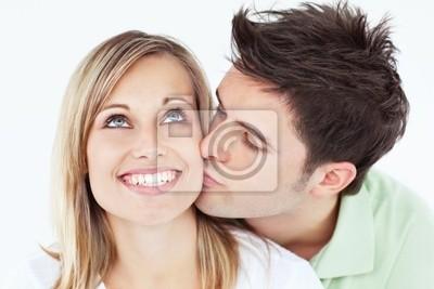 Sorgfältige Mann küsst seine Freundin lächelnd vor einem weißen backg