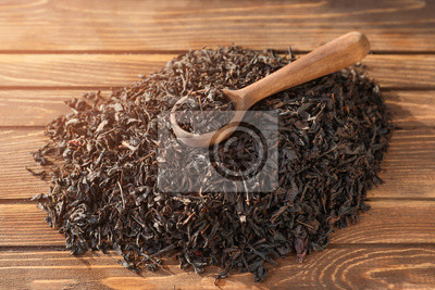 Bild Spoon and heap of dry tea leaves on wooden background
