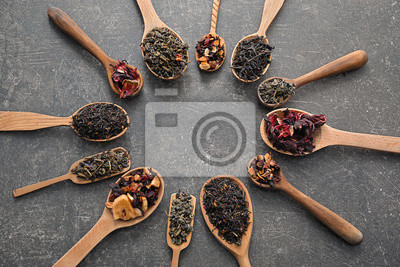 Bild Spoons with different types of dry tea leaves on grey background