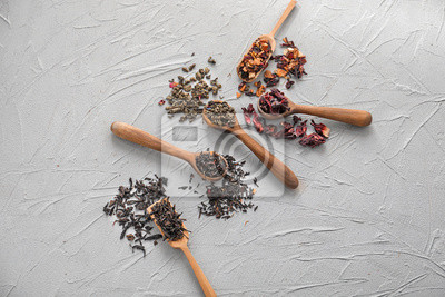 Bild Spoons with different types of dry tea leaves on light background