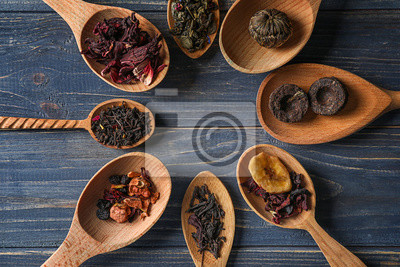 Bild Spoons with different types of dry tea leaves on wooden background