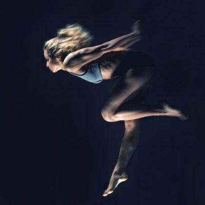 Sport, schlankes junges Mädchen mit muskulösen Körper macht einen Sprung auf einem bla