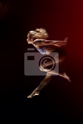 Sport, schlankes junges Mädchen mit muskulösen Körper macht einen Sprung auf einem schwarzen Hintergrund. Seitenansicht, Studioaufnahme, Schwarzer Hintergrund.