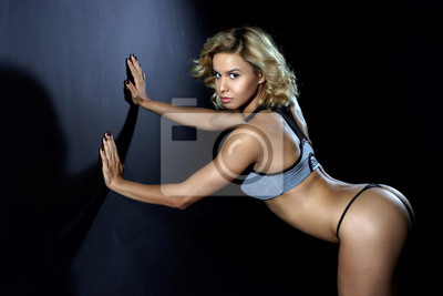 Sport, schlankes junges Mädchen mit muskulösen Körper posiert im Studio auf einem dunklen Hintergrund. Mädchen gekleidet in athletische Slips und Sport-Top. Blick in die Kamera