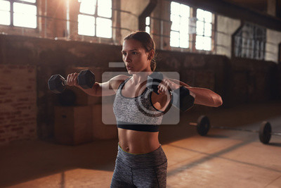 Bild Sport woman doing fitness exercise with dumbbells at gym