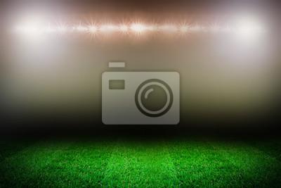 Sportfeldvorlage mit Gras und Stadionleuchten auf dem dunklen Hintergrund