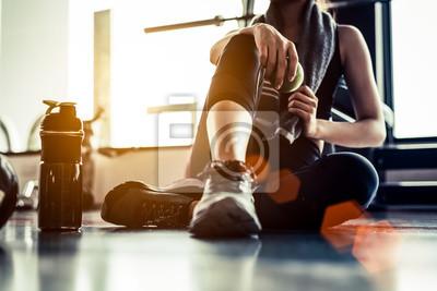 Bild Sportfrau, die nach Training oder Übung in der Eignungsturnhalle mit Proteindrink oder Trinkwasser auf Boden sitzt und stillsteht. Entspannen Sie sich Konzept. Krafttraining und Body-Building-Thema. W