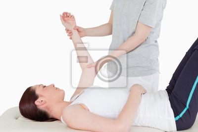 Sportlerin mit ihrem Arm gestreckt durch eine Masseurin